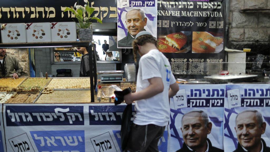 Un israelí pasa junto a carteles con el retrato del primer ministro, Benjamin Netanyahu, en el mercado de Mahané Yehudá en Jerusalén el 8 de abril de 2019, un día antes de las elecciones. Thomas Coex / AFP