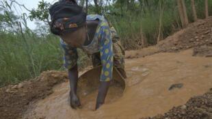 Une femme recherche de l'or non loin de la mine de Naréna.