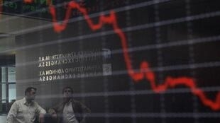 Employees at the Athens Stock Exchange are reflected in a board displaying stock prices