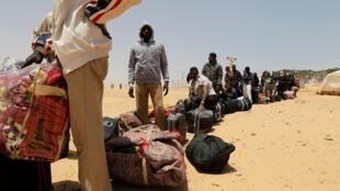 Africanos fazem fila à espera de transporte para campo de refugiados em Shusha.