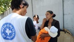 Assistente da organização Médicos do Mundo atende famílias expulsas de um acampamento na região parisiense.