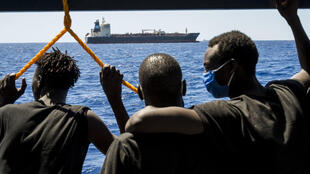 Migrants onboard a different ship in the Mediterranean look at the Maersk Etienne freighter on August 27