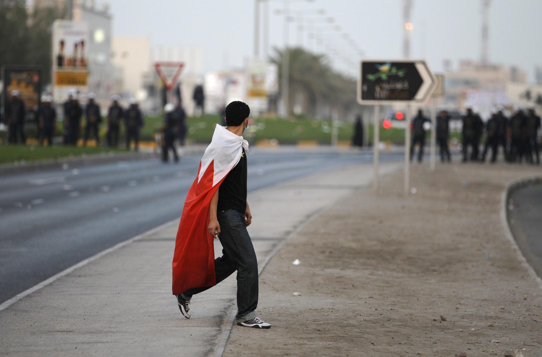 Un manifestant opposé au régime sunnite, recouvert d'un drapeau du Bahrein, le 8 juin 2012.
