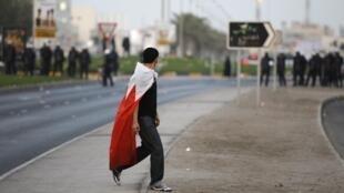 Un manifestant opposé au régime sunnite, recouvert d'un drapeau du Bahreïn, le 8 juin 2012.