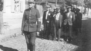Policier lituanien avec des prisonniers juifs en juillet 1941.