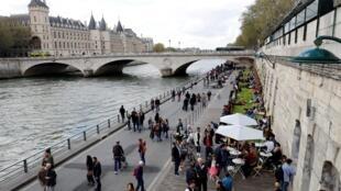 """Pessoas caminham na margem direita do Rio Sena, em Paris, durante o lançamento oficial do parque """"Rives de Seine"""" em 2 de abril de 2017."""