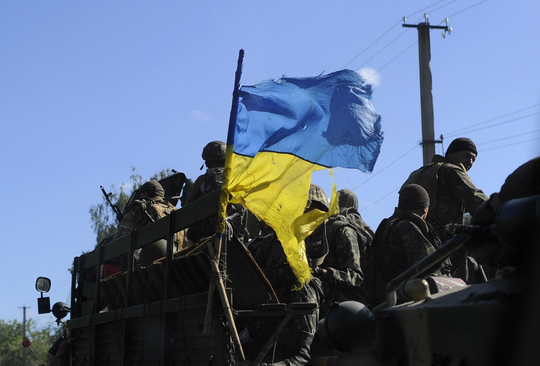 Soldados com a bandeira ucraniana em um posto de controle próximo de Slaviansk