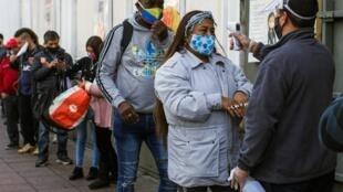 Des Chiliens font la queue devant un supermarché de Valparaiso où un employé contrôle la température corporelle des clients le 12 juin 2020.