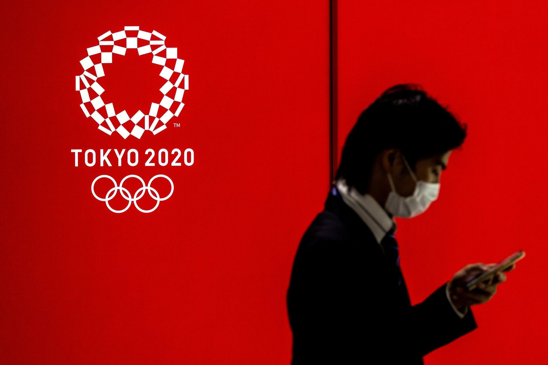 Un hombre con mascarilla pasa junto t un logotipo de los Juegos Olímpicos de Tokio, el 15 de julio de 2021 en la capital japonesa