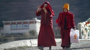 Monges budistas tibetanos caminham em estrada próxima à cidade de Daofu, onde vêm sofrendo violenta repressão armada das tropas chineses.