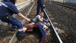 Des policiers hongrois tentent de maîtriser un couple de Syriens qui refusent d'entrer dans un camp de réfugiés à Bicske, en Hongrie, ce jeudi 3 septembre 2016.