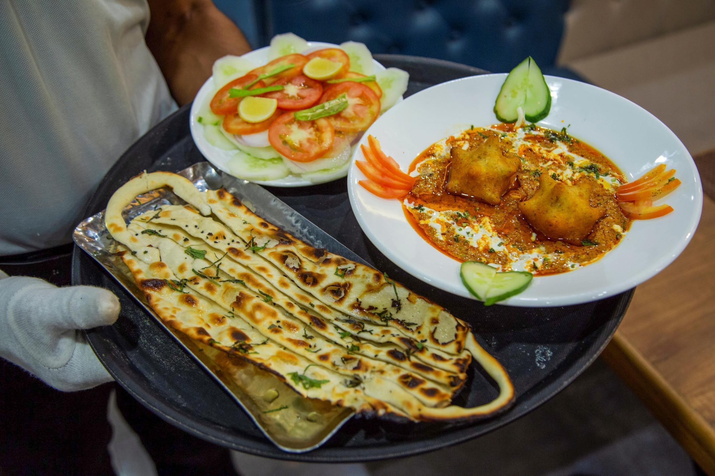 """A waiter carries """"COVID curry"""" and """"mask naan"""", two coronavirus-themed dishes, to customers at a restaurant in Jodhpur"""
