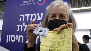 An Israeli medical worker presents her certificate of vaccination after receiving a second Pfizer-BioNTech COVID-19 shot, but the issue of virus passports has divided Europe