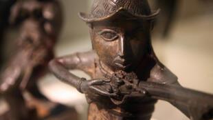 Uma estátua que representa um homem português a segurar uma espingarda (Benin, sul da Nigéria, século XVI).