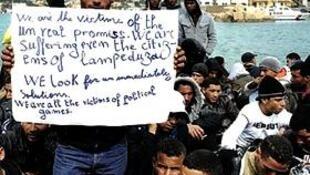 """Manifestação de tunisianos em Lampedusa , comentário do cartaz:""""Nós somos todos vítimas de uma promessa ireal(...)vítimas de jogos políticos""""."""