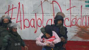 Arrestation à Caracas pendant une manifestation contre le gouvernement du président Maduro à Caracas le 28 juillet 2017. Sur le mur, on peut lire: «A bas la dictature».