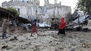 Somali women walk past the site of a deadly blast in Mogadishu 14 April 2013