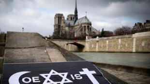 Les symboles des trois grandes religions monothéistes (judaïsme, islam, catholicisme) sont utilisés par l'artiste Combo pour écrire le mot «Coexist», dans les rues de Paris, non loin de l'Institut du monde arabe.