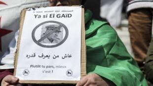 Un manifestant tient une pancarte demandant le départ du chef d'état-major Ahmed Gaïd Salah.