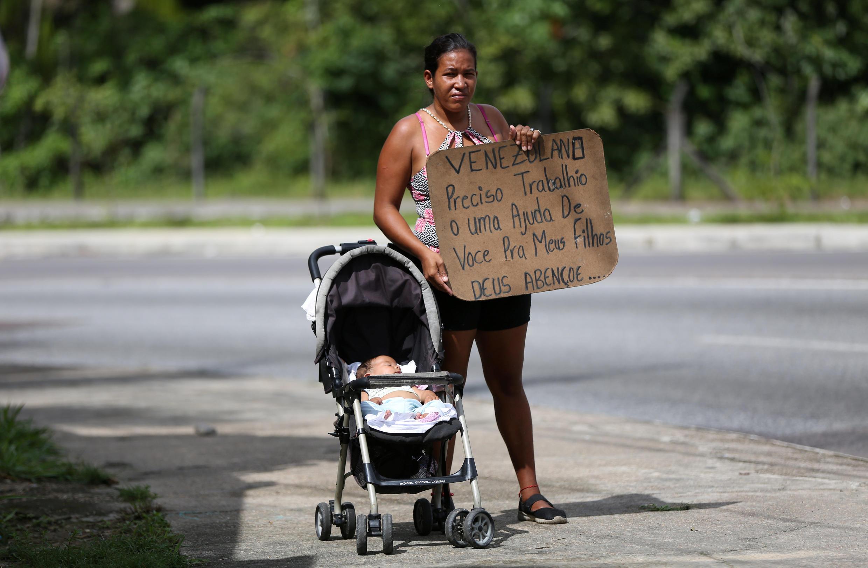 Nhiều triệu dân Venezuela đã phải tha phương cầu thực. Trong ảnh: Một phụ nữ mang tấm bảng xin việc làm hoặc trợ giúp để nuôi con, tại Manaus, Brazil, 14/01/2019.
