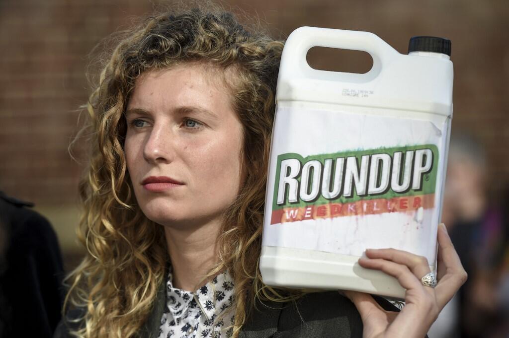 Una mujer muestra un bidón de Roundup, un herbicida que contiene glifosato, durante una manifestación de apoyo al alcalde bretón Daniel Cueff, quien fue el primero en adoptar un decreto antipesticidas. 22 de Agosto de 2019.