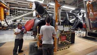 Funcionários montam veículos na linha de montagem da fábrica de automóveis da SEAT em Martorell.