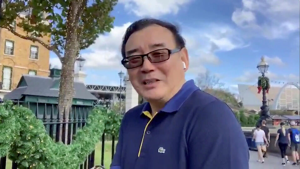 Australian writer Yang Hengjun wishes Happy New Year to his Twitter followers at an unidentified location in this still image from an undated video obtained via social media.