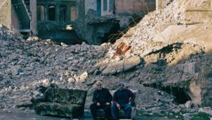 Dos iraquíes sentados en medio de los escombros de Mosul, en el norte de Irak, el 18 de enero de 2021