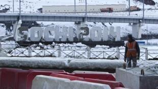 Un travailleur se tient près des barrières de sécurité à la station de Krasnaya Polyana, près de la ville de Sotchi, le 24 décembre 2013.