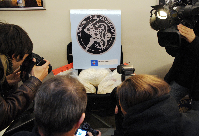 Будничная картинка: парижская бригада по борьбе с наркоторговлей презентует очередную обнаруженную партию кокаина на фоне своей эмблемы