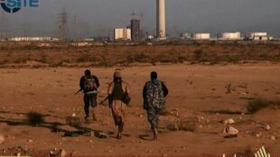 Sur cette capture d'écran vidéo, réalisée par l'agence américaine de surveillance Site à partir d'un média jihadiste, trois combattants supposés appartenir au groupe Etat islamique courent vers une centrale électrique dans la ville de Syrte, le 9 juin 2015
