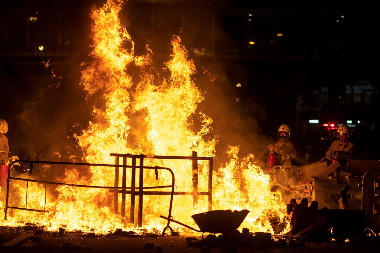 香港特首林鄭月娥頒布『禁蒙面法』後引發激烈抗議,圖為消防隊員試圖撲滅抗議者在黃大仙區附近點燃的火。
