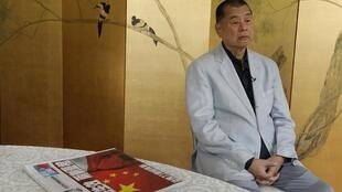 Media mogul Jimmy Lai poses next to a copy of the Apple Daily during an interview on 1 July at his home.