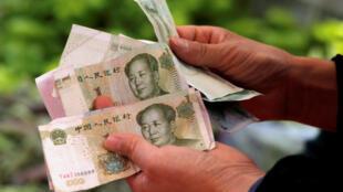 图为一名消费者在一家北京菜市场点数人民币。