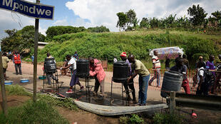 People from DRC wash their hands at Ebola screening point set up at Ugandan border