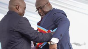 Cérémonie d'investiture du nouveau président de la RDC à Kinshasa, le 24 janvier 2019: le président sortant Joseph Kabila (g.) remet l'écharpe présidentielle à son successeur Félix Tshisekedi.