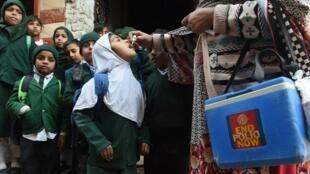 Une femme vaccine une petite fille contre la polio le 15 janvier 2018 à Lahore au Pakistan.