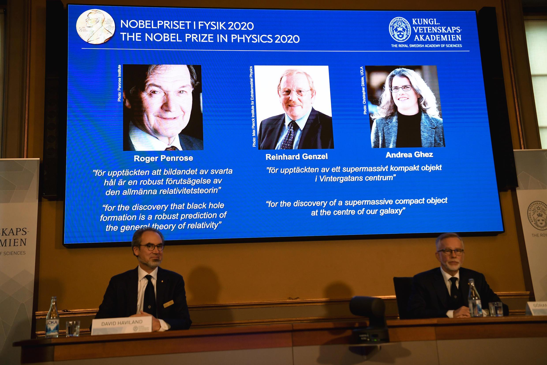 Una pantalla proyecta las imágenes de los tres ganadores del Premio Nobel de Física 2020, tras su anuncio en la Real Academia Sueca de Ciencias, el 6 de octubre de 2020 en Estocolmo