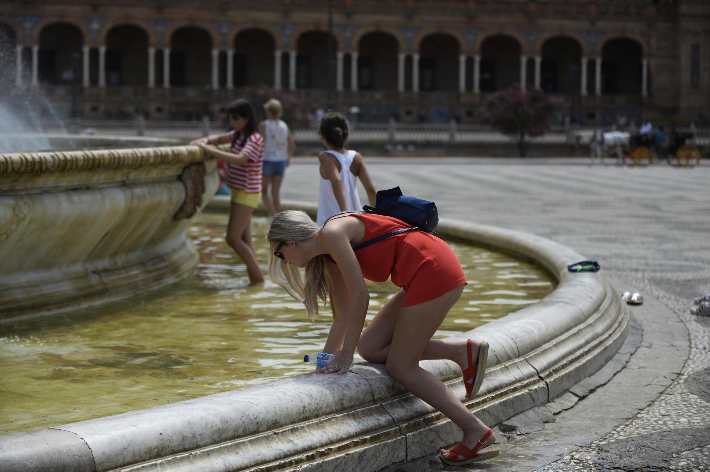 Une femme se rafraîchit dans une fontaine à Séville, en Espagne, frappée de plein fouet par la canicule le 1er août 2018.