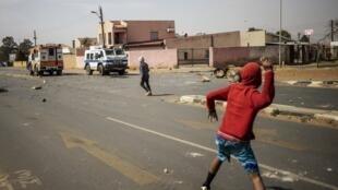 Des habitants jettent des pierres sur la police sud-africaine après la mort d'un adolescent à Eldorado Park, le 27 août 2020.