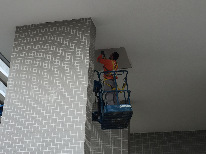 Operário repara um problema de vazamento no térreo do prédio da delegação colombiana.