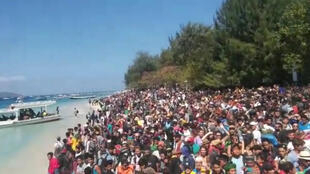La gente se amontona en las orillas de la isla Gili Trawangan para huir, Indonesia, este 6 de agosto de 2018.
