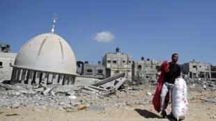 Wani Bafalasdine a kusa da Masallacin da aka tarwatsa dauke da wasu da kayansa da ya tsira da su a gidansa  a Khuzaa da ke kudancin Zirin Gaza.