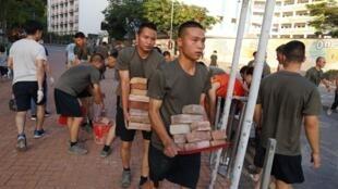 Os soldados do Exército Popular de Libertação (EPL) em Hong Kong ajudam a limpar as ruas do território chinês, neste sábado 16 de novembro de 2019.
