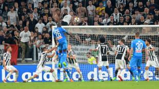 Le joueur napolitain Kalidou Koulibaly ouvre le score de la tête contre la Juventus de Turin lors d'un match de Serie A à Turin, en Italie, le 22 avril 2018.