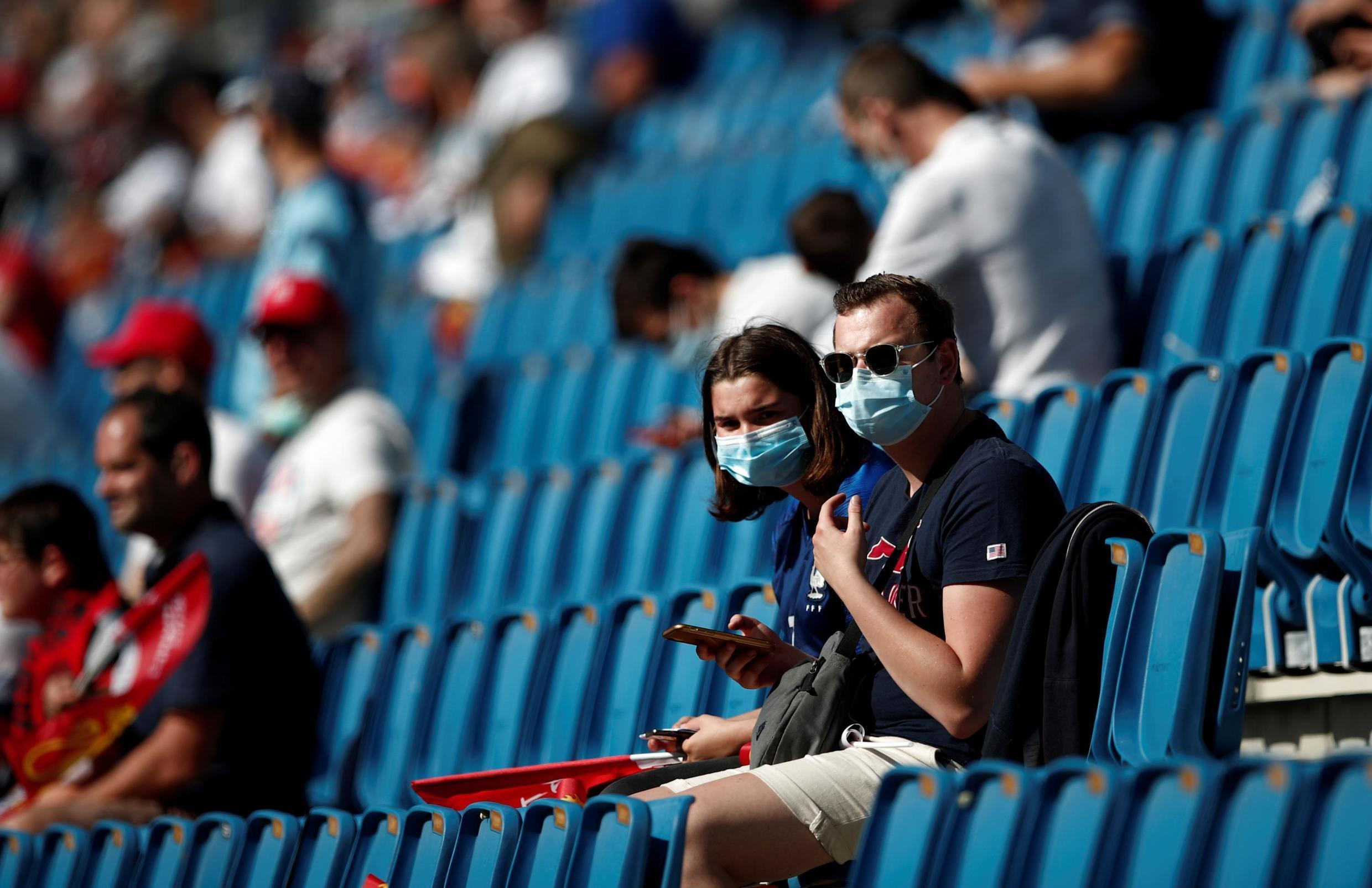 Some but not all French football spectators wear protective masks at the match between Le Havre and Paris Saint-Germain on Saturday. French officials are considering whether to impose masks in indoor locations.