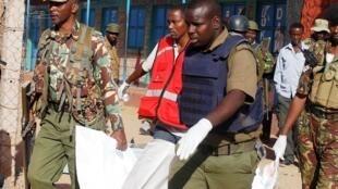 """مأمورین پلیس و صلیب سرخ کنیا در حال حمل جسد فردی که در یورش شبانه اسلامگرایان مسلح """"الشباب"""" کشته شده ."""