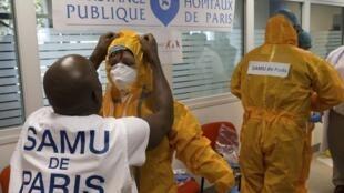 Сотрудники французской скорой помощи в защитных костюмах от Эболы, презентация для журналистов в больнице Некер, Париж, 24 октябяря 2014 г.