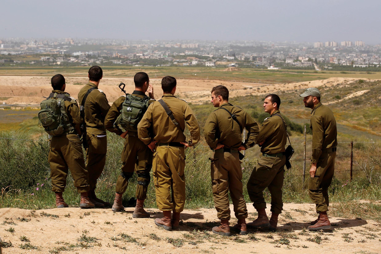 Des soldats israéliens écoutent le briefing de leur supérieur du côté israélien de la frontière qui sépare l'Etat hébreu de la bande de Gaza le 29 mars 2018.