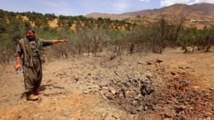 Un miembro del PKK frente a un cráter dejado por un bombardeo turco, Qandil, norte de Irak